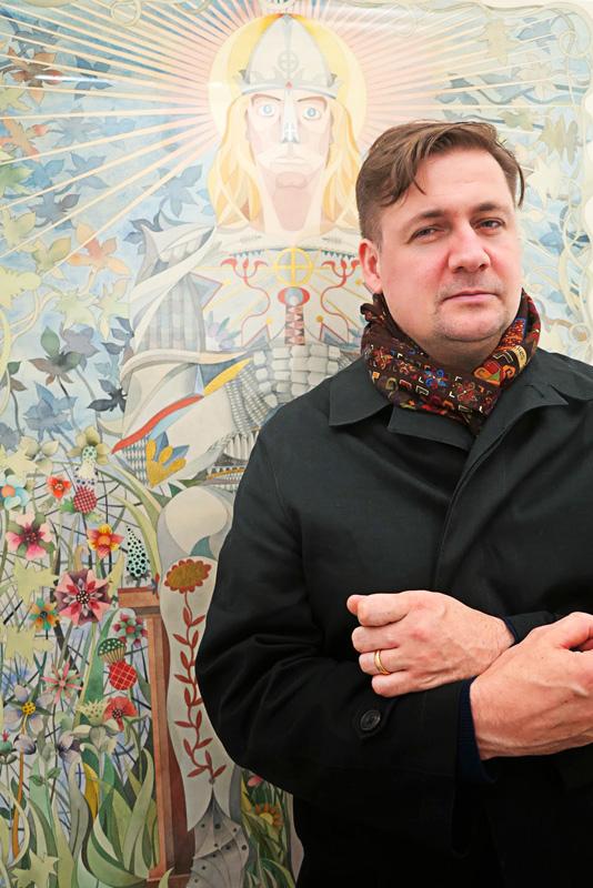 L'artiste posant devant l'une de ses œuvres.